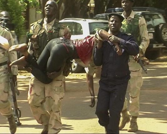 Personal de emergenciasde Mali traslada a una mujer herida a su salida del hotel de lujo Radisson.