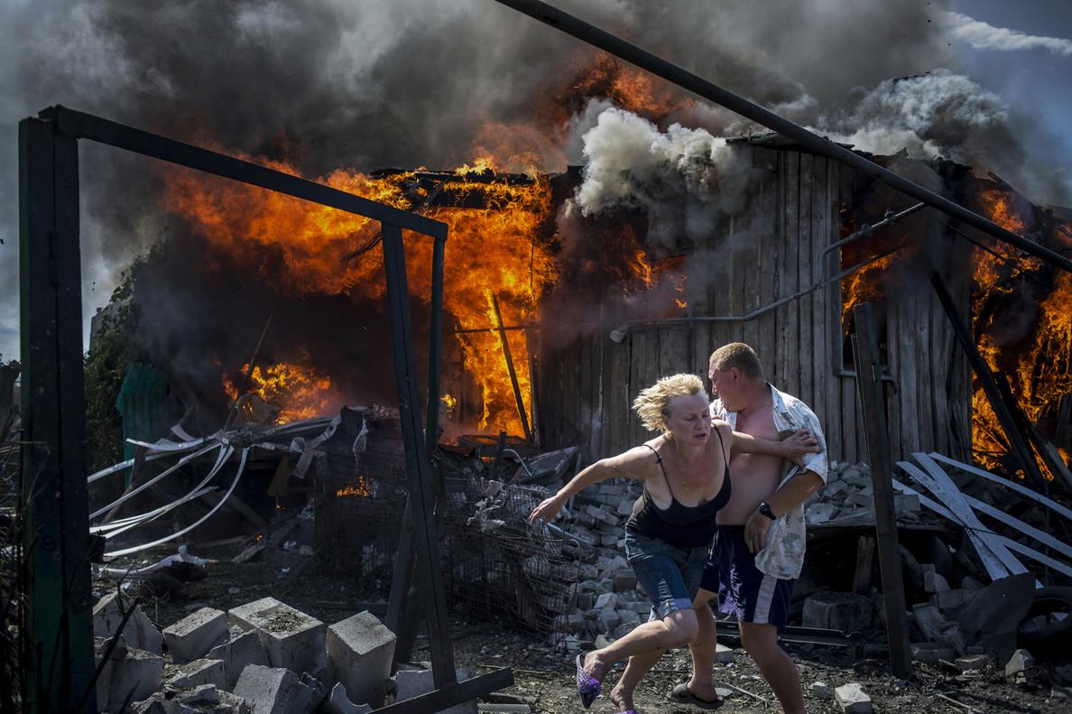 Los días negros de Ucrania, deValery Melnikov, donde se ven civiles escapando de un incendio en una casa destruida por un ataque aéreo en un pueblo Luhanskaya.