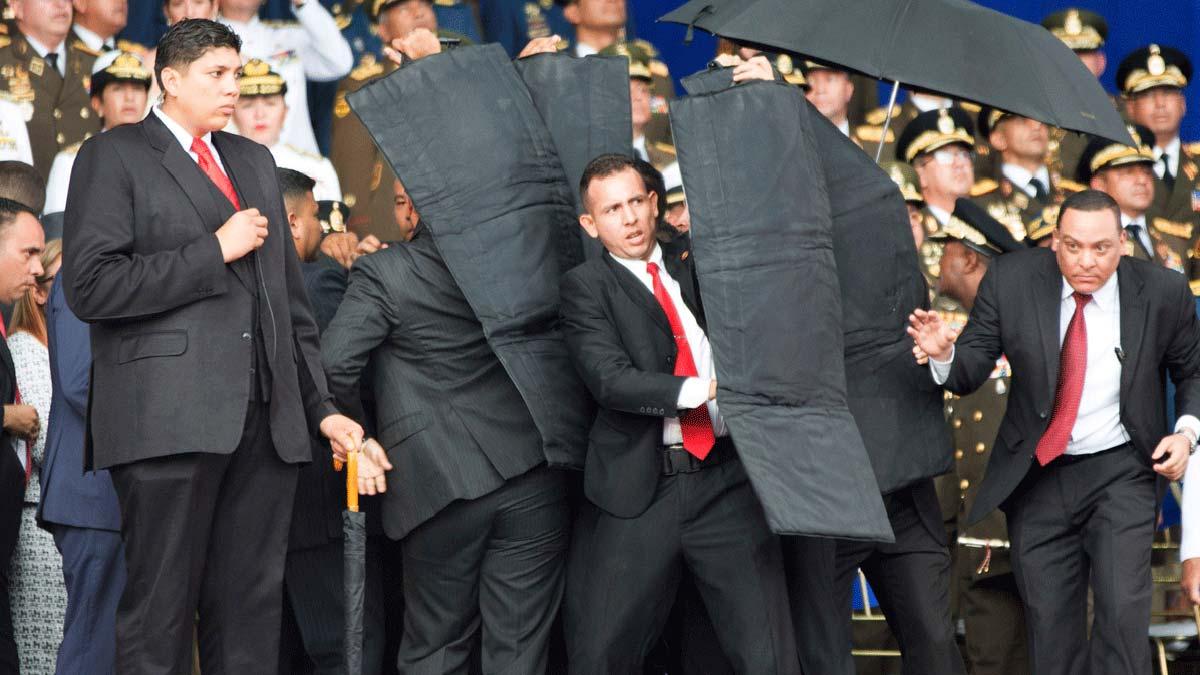 Los escoltas protegen al presidente Maduro tras la explosión de los drones.