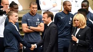 Los Macron saludan a Griezmann, acompañado por Mbappé.