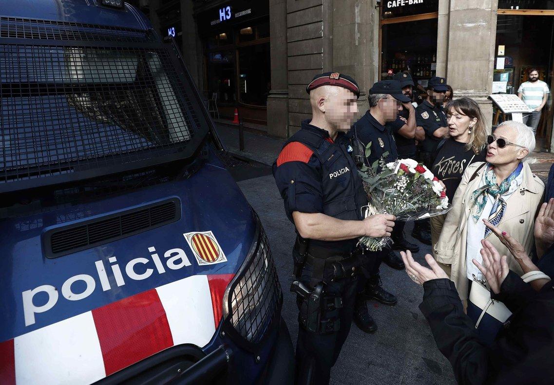 Un mossorecoge un ramo de flores entregado este mediodía en la Jefatura de la Policía Nacional de Via Laietana.