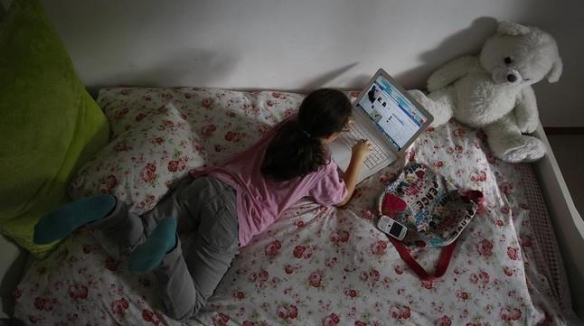 Una menor con un ordenador, en su habitación.
