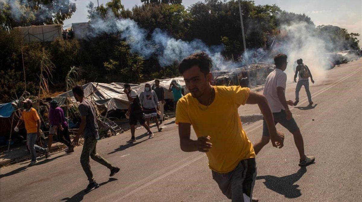 Refugiados de Moria huyen de los gases lacrimógenos lanzados por la policía griega.