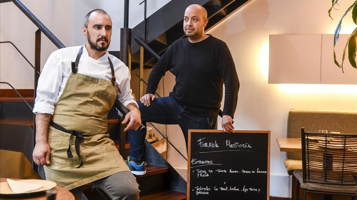 En la escalera, Javier Vallscon el cartel del menú de mediodía y, al pie, Adrián Rubio.