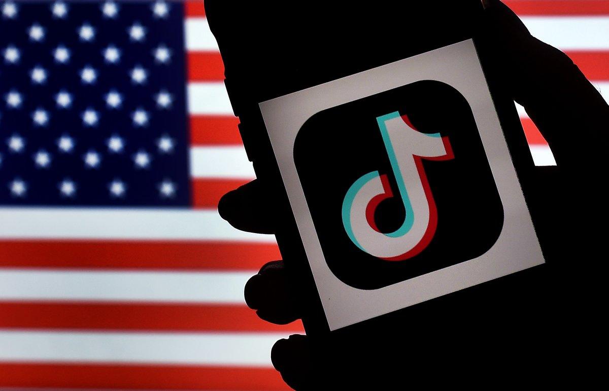 El logo de TikTok sobre una bandera de Estados Unidos.