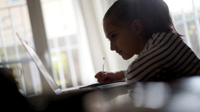Todos los alumnos españoles pasarán de curso este año. En la foto, una niña hace los deberes en su casa.