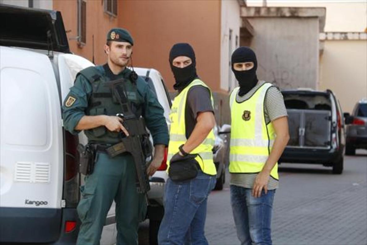 Dos agentes de la Guardia Civil y uno de los Mossos trabajan conjuntamente en una operación antiterrorista.