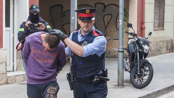 Un mosso traslada al coche policial a uno de los dos detenidos tras el registro de su piso.