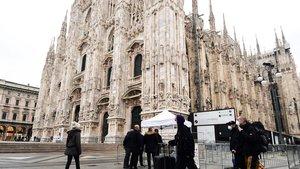 Turistas con mascarillas pasan por delante de la catedral de Milán, en Lombardía.