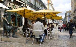 Turistas en Lisboa junto a la estatua de Fernando Pessoa.