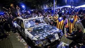 Uno de los coches de los guardias civiles que registraban la consellería de Economía de la Generalitat, destruido durante la concentración que convocaronla ANC y Òmnium Cultural a la puerta del edificio registrado.
