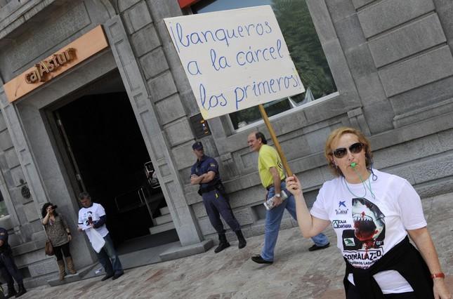 Una mujer protesta ante la sede de Cajastur (Liberbank) en Oviedo.