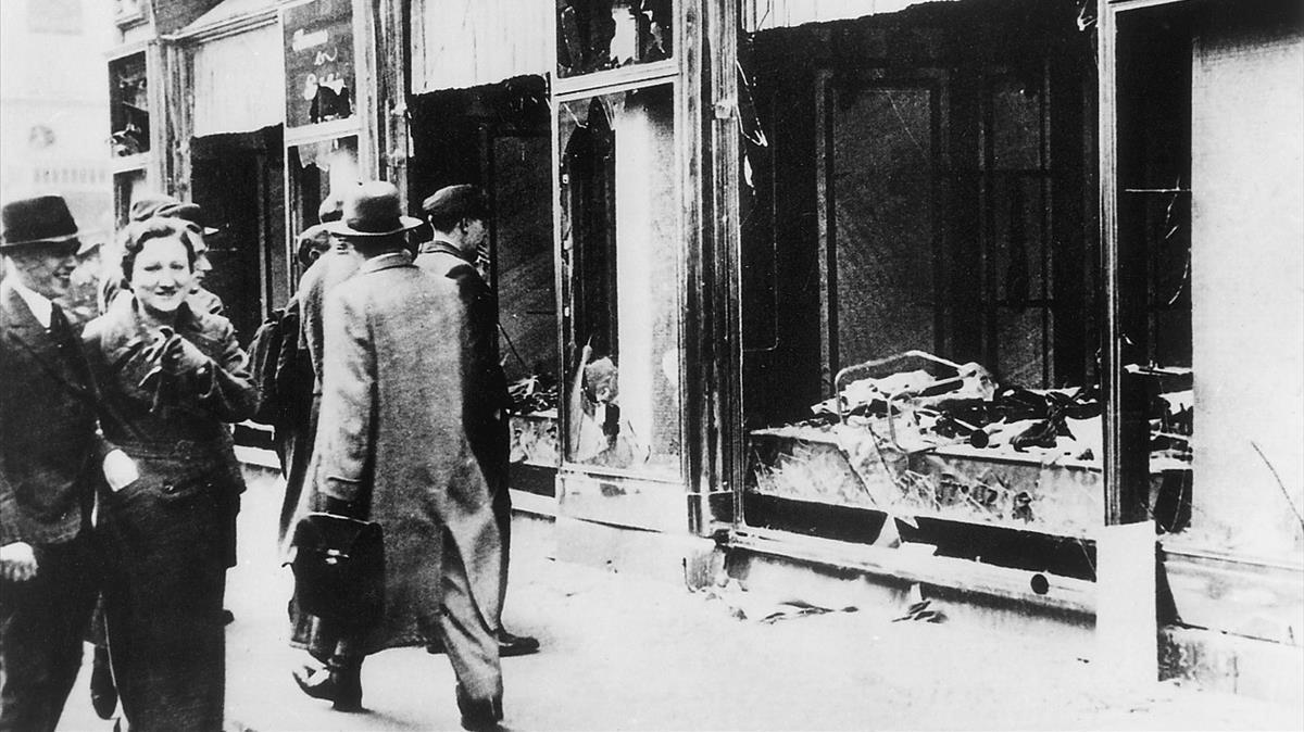 Transeúntes indiferentes ante una tienda judía destruida y saqueada en la Alemania nazi.