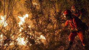 Unos bomberos luchan contra el fuego en Vilamarin, en Galicia