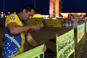 Un partidario de Rousseff clava un cartel en las afueras del senado brasileño.
