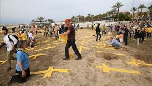 La plantada de cruces en la playa de Mataró se hace con telas amarillas