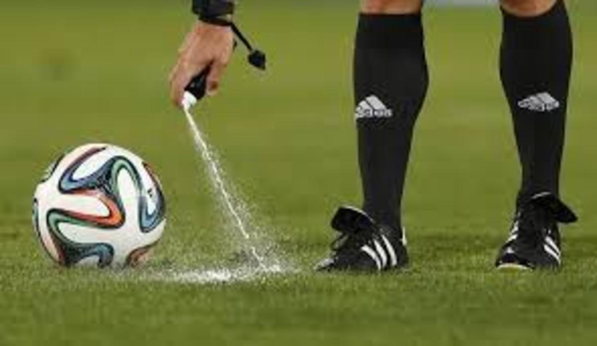 Un árbitro usando spray para marcar el lugar desde donde lanzar la falta
