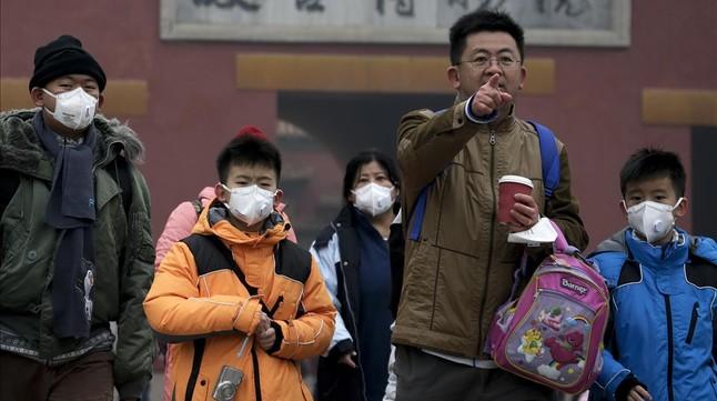 Un grupo de turistas visita Pekín protegiéndose contra la polución