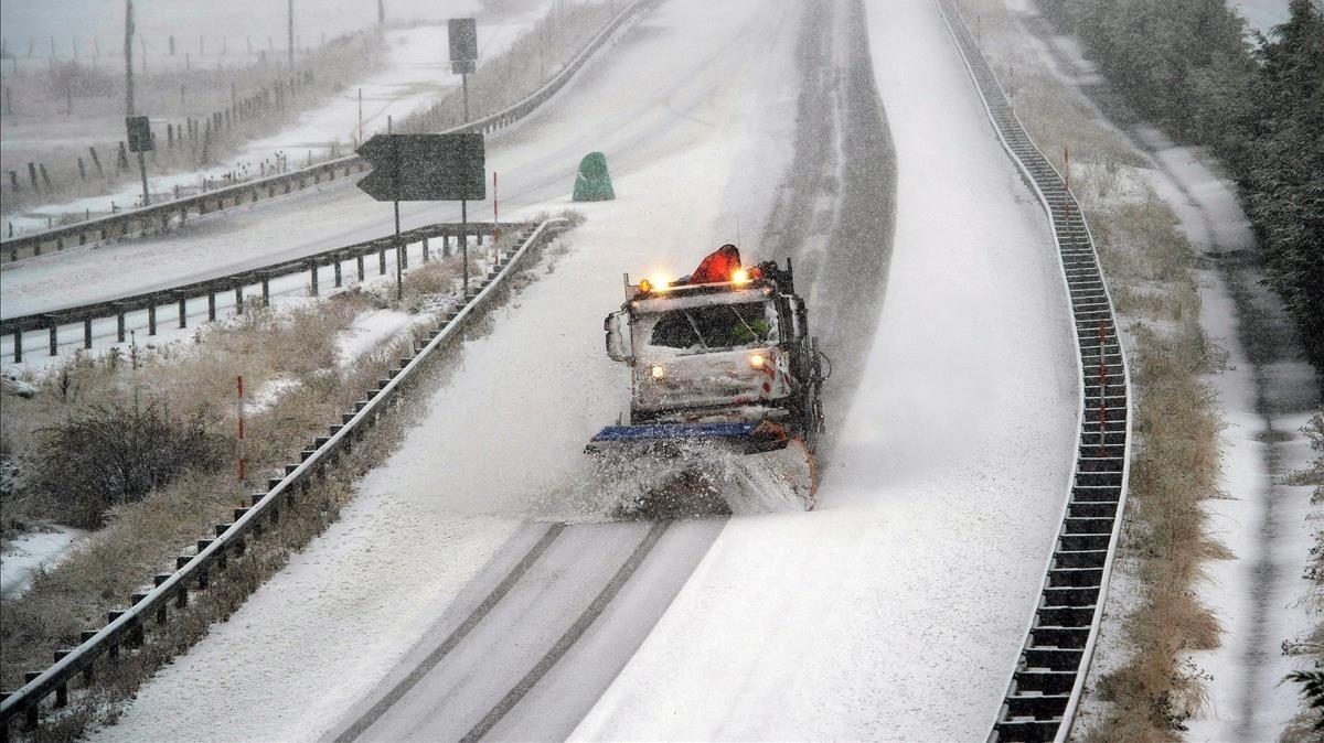 Un camión quitanieves limpia la autopista A-67 a la altura de la localidad cántabra de Reinosa.