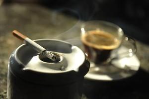 Un cigarrillo humea junto a una taza de café en un bar.