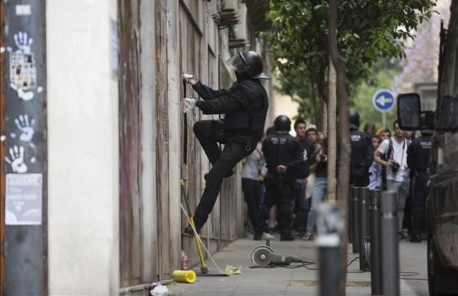 Un mosso accede al 'banco expropiado' por un agujero abierto por el lateral del local por la propia policía.