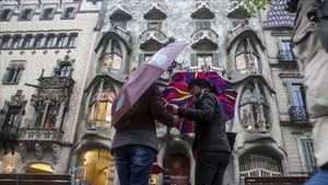 Dos chicas con paraguas frente a la Casa Batlló, en Barcelona.