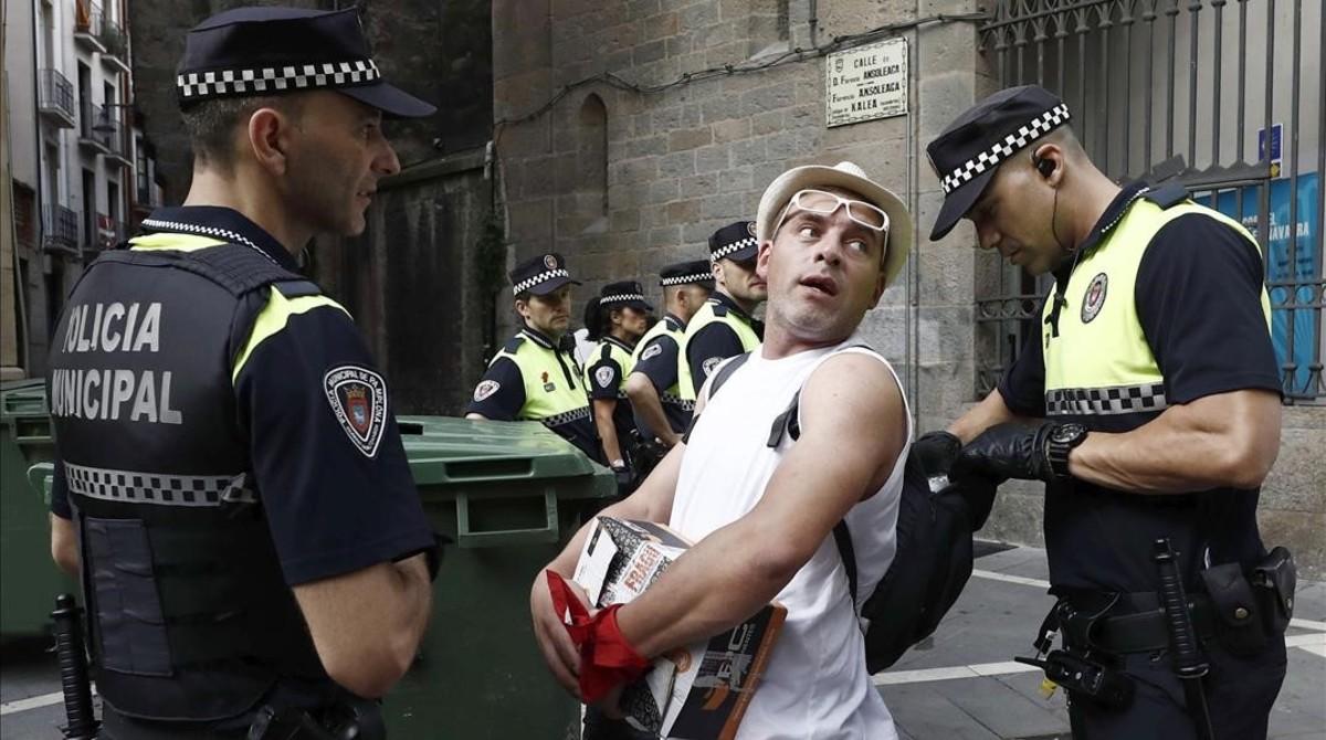 Efectivos de la Policia Municipal registran la mochila de un joven.