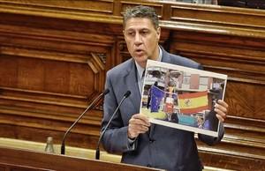 Albiol muestra en el Parlament una foto en la que unos anticapitalistas queman banderas de España, la UE y Francia en la Diada.
