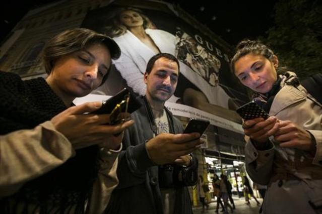 Un grupo de turistas argentinos consultan sus móviles, en Barcelona.