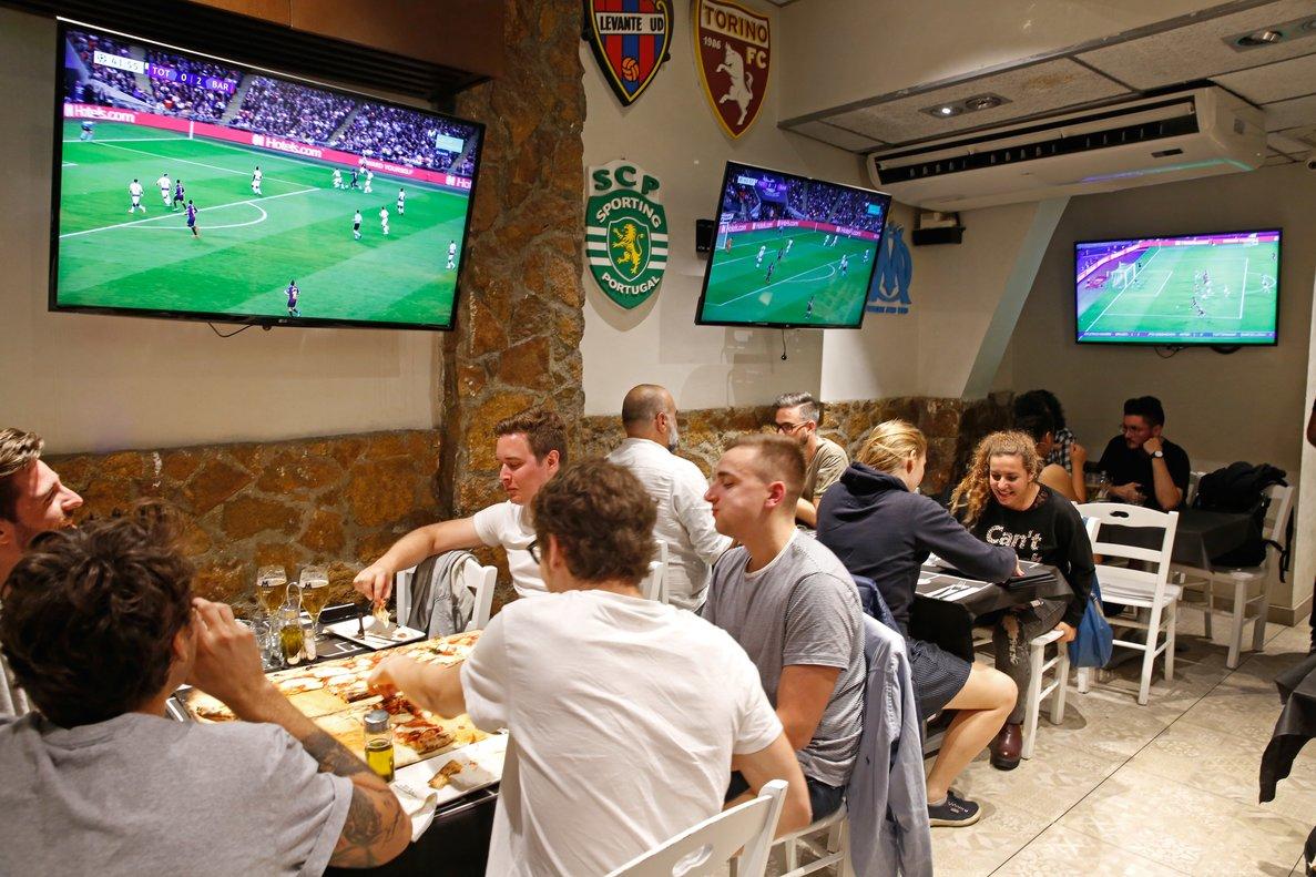 Grupos de jóvenes viendo el fútbol en un bar, en una imagen de archivo.