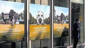 Un hombre, ante una oficina de Bankia, con publicidad sobre sus hipotecas.