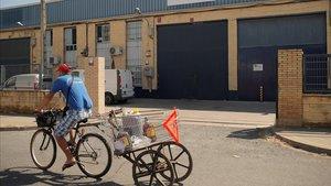 Un hombre pasa en bicicleta por delante de la empresa Magrudis en Sevilla, cerrada por su vinculación al brote de listeriosis.