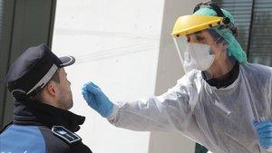 Personal sanitario realiza una prueba a un policía municipal de Madrid.