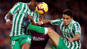 Malcom, encerrado entre Junior y Bartra, antes de ser sustituido en el Barça-Betis.