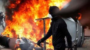 Un manifestante pasa junto a un coche en llamas, durante los disturbios del Primero de Mayo en París.