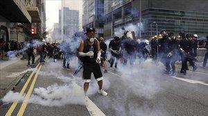 Manifestantes frente a los gases lacrimógenos lanzados por la policía en Hong Kong.
