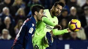 Messi prueba un centro ante Campana en el partido ante el Levante.