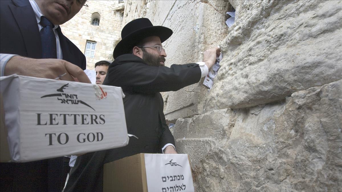 Un rabino deja cartas destinadas a Dios en el Muro de las Lamentaciones en Jerusalén.