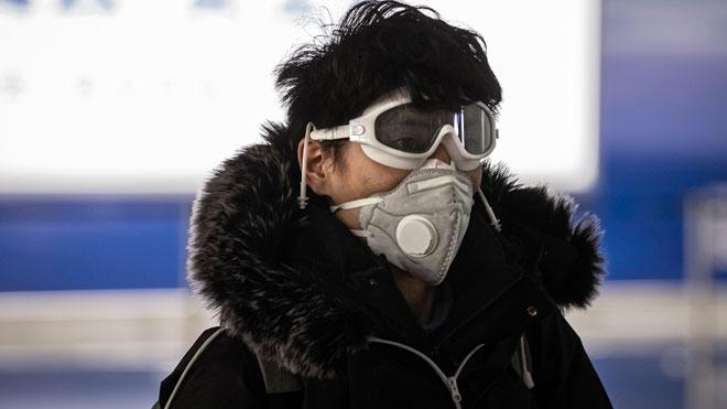 La OCDE rebaja al 2,4% su previsión de crecimiento por el coronavirus. En la foto, un hombre en el aeropuerto de Beijing.