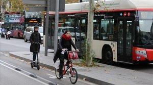 Patinetes, bicis y un autobús de transporte público, en Barcelona.