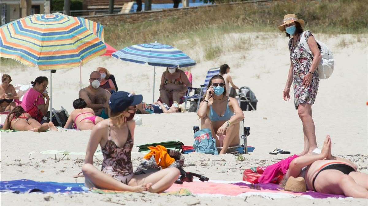 Personas protegidas con mascarillas en la playa de A Rapadoira, en Foz, en la comarca de A Marina (Lugo).
