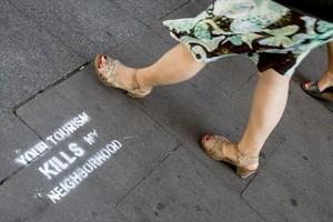 Pintada contra el turismo invasivo y los pisos turísticos en una calle de la Barceloneta.