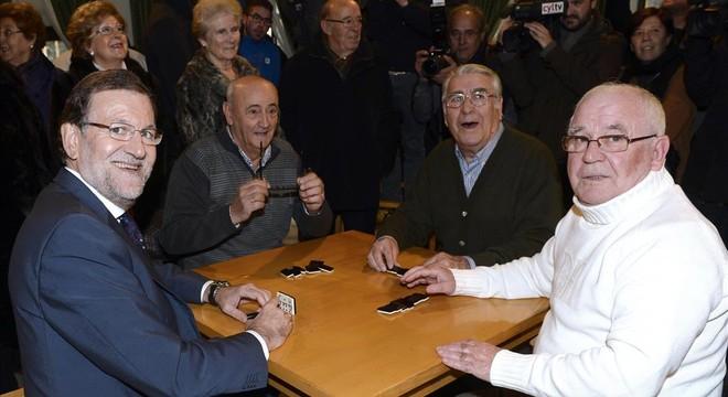 Rajoy da un mitin en un banco y juega al dominó en busca del voto del jubilado