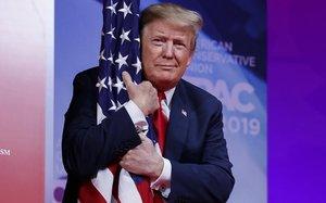 El presidente Donald Trump abraza la bandera de Estados Unidos en la Conferencia de Acción Política Conservadora.