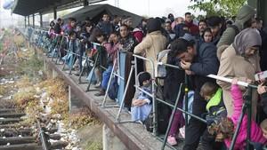 Un grupo efugiados esperan en un anden un tren especial en la principal estación de tren de Pasau en Alemania, en octubre del 2015.