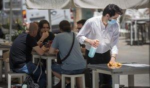 Un camarero desinfecta la mesa de una terraza, el pasado lunes.