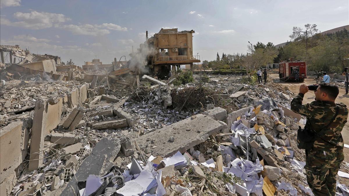 Un soldado sirio toma fotos de los escombros de un edificio bombardeado en la operación liderada por EEUU, que formaba parte del Centro de Estudios e InvestigacionesCientíficas, en Damasco, este sábado.