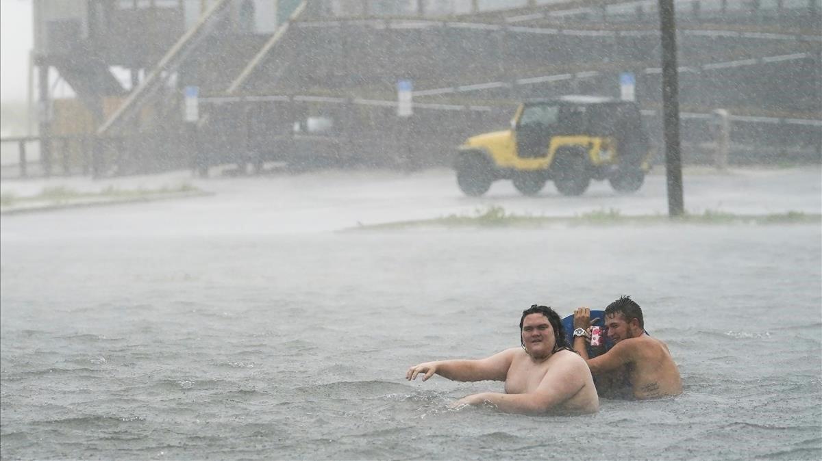 Unas personas en un parking inundado en Navarre Beach.