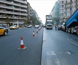 Unos obreros realizan obras de asfaltado en un tramo de la avenida Diagonal y, a la derecha, imagen del volcado de asfalto en un tramo de la calle de Aragó, ayer.