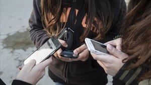 Adolescentes, con sus teléfonos móviles.